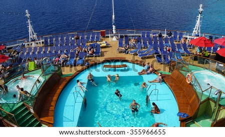MIAMI, FL - NOV 21: Poolside on the Carnival Breeze docked in Miami, Florida, on Nov 21, 2015. The Breeze is a Dream-class cruise ship owned by Carnival Cruise which entered service in June 2012. - stock photo