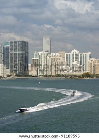 Miami Florida, Brickel downtown residential and office buildings and hotels, with Biscayne bay waters and cloudy sky and speed boats moving. Famous travel location. - stock photo