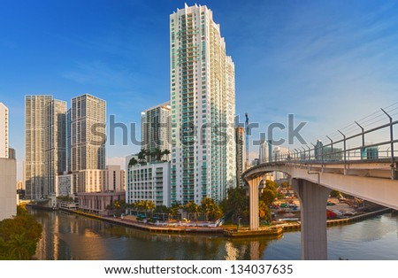 Miami Florida, Brickell and downtown financial buildings and train bridge over miami River on a beautiful summer day with blue sky