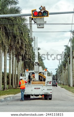 MIAMI, FLORIDA - January 13, 2015: Electrical workers are busy repairing a broken traffic light on a busy intersection. - stock photo