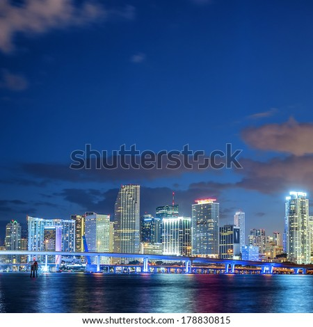 Miami Florida, sunset with colorful illuminated business and residential buildings and bridge on Biscayne Bay  - stock photo