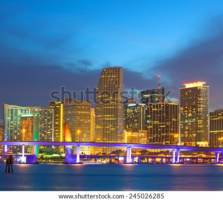 Miami Florida USA, sunset or sunrise over the city skyline of downtown business and residential illuminated buildings, with colorful clouds and reflections in the water of Biscayne Bay,  - stock photo