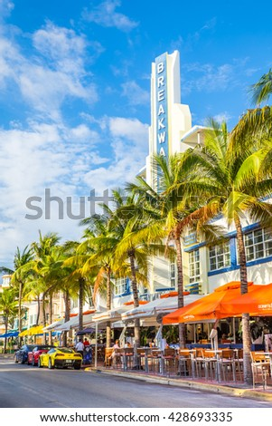 MIAMI, FLORIDA - View along Ocean Drive along South Beach Miami in the historic Art Deco District with hotels, restaurant and luxury cars visible