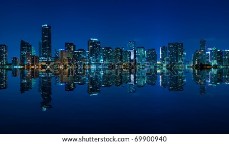 Miami skyline at night - panoramic image with beautiful water reflections - stock photo