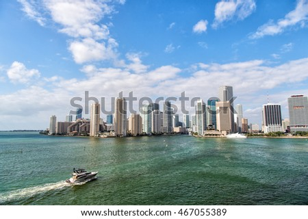 Miami skyscrapers with blue cloudy sky, boat sailing next to Miami downtown. Aerial view