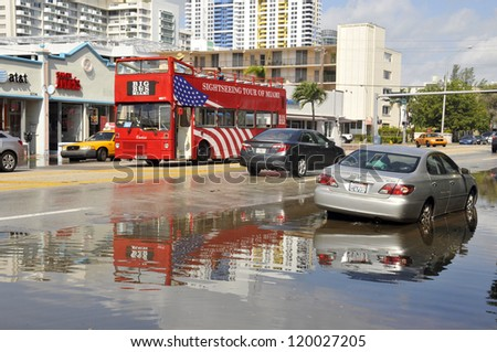 MIAMI - SOUTH BEACH - FLORIDA, OCTOBER 28: People in tourists bus watch Miami South beach Lenox Ave flood aftermath of Hurricane Sandy on october 28 2012 in Miami South Beach. - stock photo