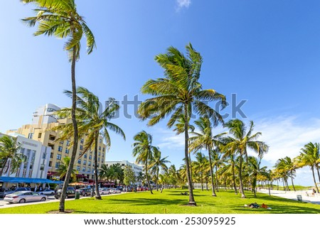 Miami, USA - AUG 1, 2013: people relaxing at beautiful Miami Beach, popular travel destination, wide angle view cityscape with palm trees and art deco architecture in Miami, USA. - stock photo