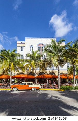 MIAMI, USA - AUG 5, 2013: The Art Deco Edison Hotel and a classic oldsmobile car on Ocean Drive, South Beach, Miami, USA. Classic cars are allowed to park at yellow line.
