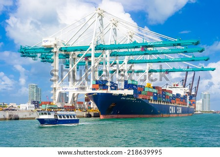 MIAMI,USA - AUGUST 26, 2014 : Ship with containers unloading cargo at the Port of Miami assited by big modern cranes - stock photo