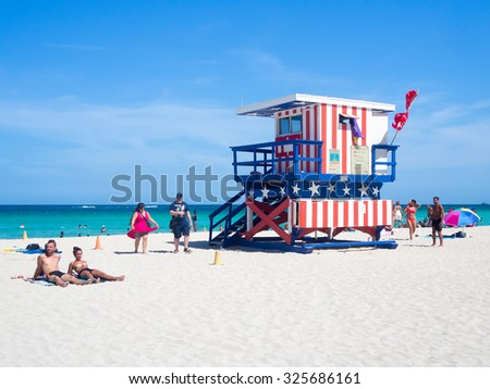 MIAMI,USA - AUGUST 8,2015: Summer day at South Beach in Miami next to the famous lifeguard tower decorated with the colors of the american flag - stock photo