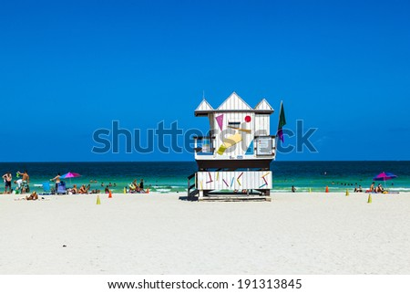 MIAMI, USA - JULY 27: people enjoy beach life on July 27, 2010 in Miami, USA. South beach is famous for its wooden lifeguard towers which are designed in Art deco style. - stock photo