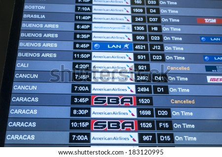 MIAMI, USA - MARCH 19, 2014: Monitor at Miami International Airport lists scheduled departing flights to Caracas, Cancun, Cali, Buenos Aires, Brasilia, and Boston and names of airlines  - stock photo