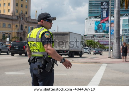 MIAMI, USA - MARCH 18, 2016: Police officer in the street regulating traffic. - stock photo
