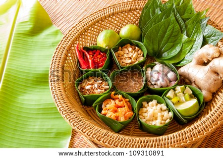 Miang Kham is a tasty snack often sold as Thailand street food. It involves wrapping little tidbits of several items in a leaf, along with a sweet-and-salty sauce. - stock photo