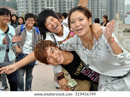 Mianyang, China - October 15, 2010:  A Group of university students ham it up on the approach bridge to the Sheng Shui Buddhist temple