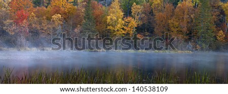 Michigamme Mist  A panoramic view of the fall colors along the Michigamme River in Michigan's Upper Peninsula. - stock photo