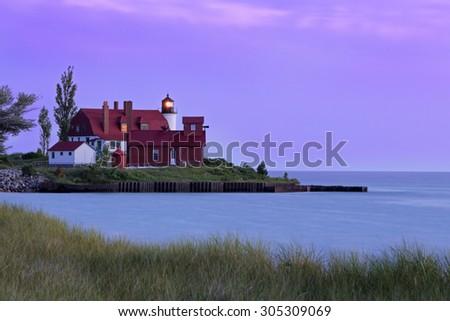Michigan's Point Betsie Lighthouse shines its light over Lake Michigan at sundown. - stock photo