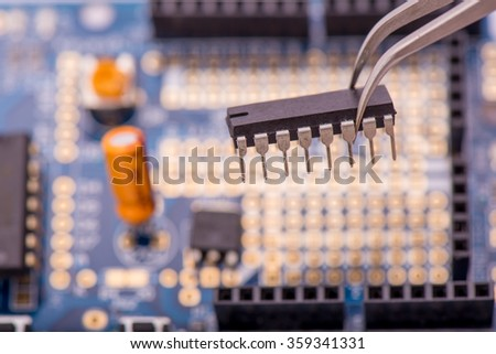 Microchip held with tweezers by an engineer over a blue motherboard  - stock photo