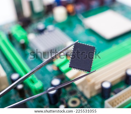 microchip in the tweezers on the background of the motherboard