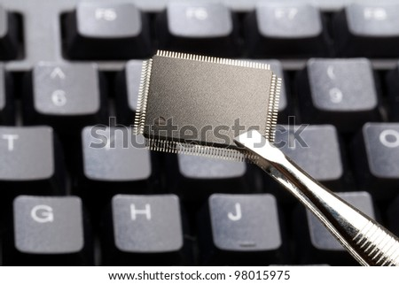 Microchip kept by a tweezers on a on a keyboard background