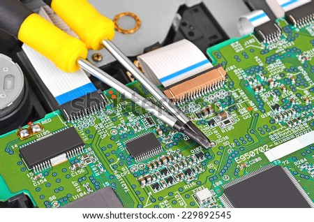 Microcircuit inside of dvd disk drive and screwdriver - stock photo
