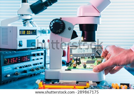 Microelectronics laboratory with the measuring instruments and microscopes. Electronic circuit board in hand - stock photo