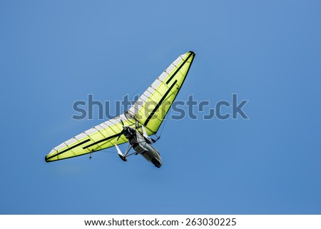 Microlight aircraft flying high against a deep blue sky. - stock photo