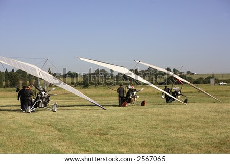 Microlights parked on a grass runway - stock photo