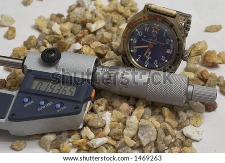 micrometer gauge coupled with analog clock - stock photo