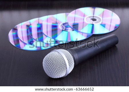 Microphone and cd disks on black table,closed-up - stock photo