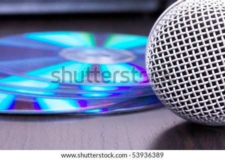 Microphone and cd disks on black table,macro - stock photo