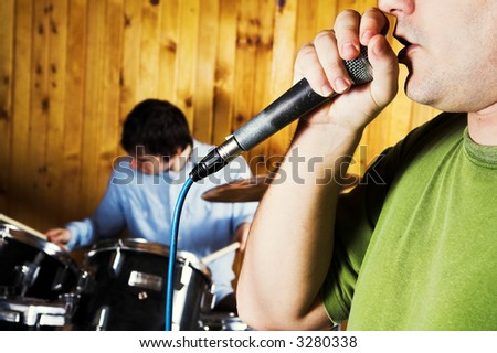 Microphone and Drummer playing behind in blur. Rock music concept - stock photo