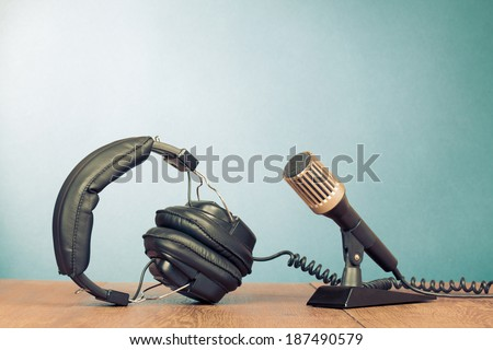 Microphone and headphones on table front mint green background - stock photo