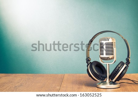 Microphone and headphones on table in front aquamarine wall background - stock photo