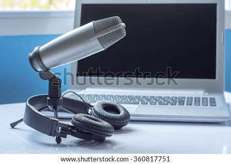 Microphone and headphones with laptop sound editing concept