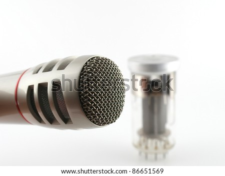 Microphone and old glass triode (valve). Shallow DOF. - stock photo