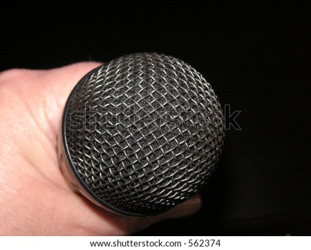 microphone being held over a dark background - stock photo