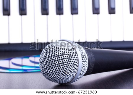 Microphone, cd disks and piano keyboard on black table,closeup