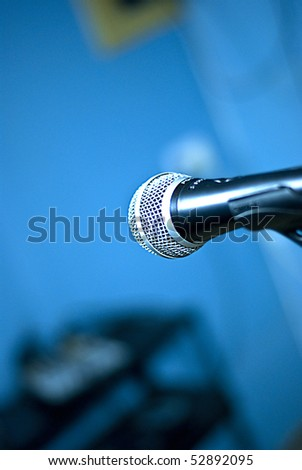 Microphone close up in recording studio with blurred blue background - stock photo