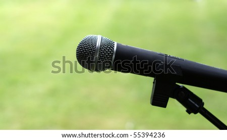 Microphone closeup outdoors with blurred green background - stock photo