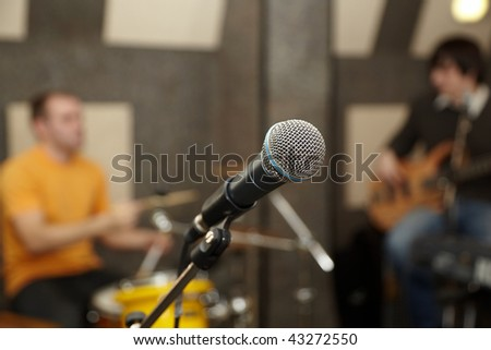 microphone. drummer and guitar player in out of focus - stock photo