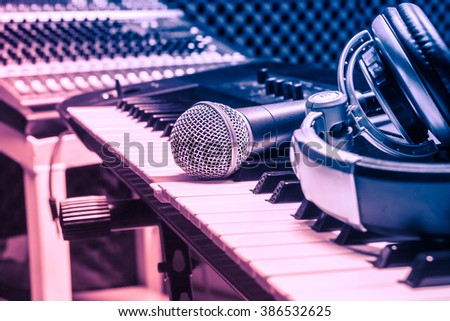 microphone,headphone on piano background.Blurred sound mixer. - stock photo