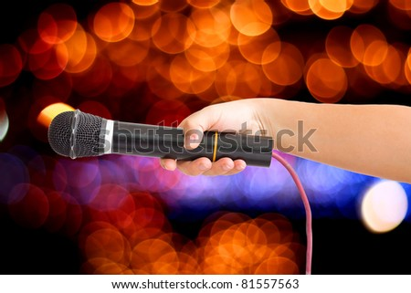 Microphone in a hand on bokeh abstract light background. save path for isolated design work - stock photo