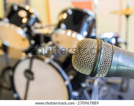 Microphone  in a recording studio or concert hall with drum in out of focus background. - stock photo