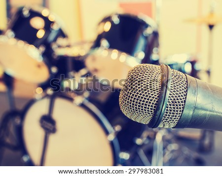 Microphone  in a recording studio or concert hall with drum in out of focus background. Vintage style and filtered process. - stock photo