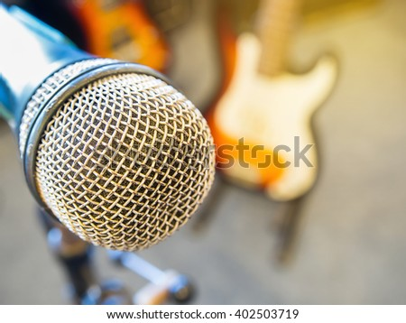 Microphone in a recording studio or concert hall with electric guitar and amplifier in out of focus background and light. : Filtered process.