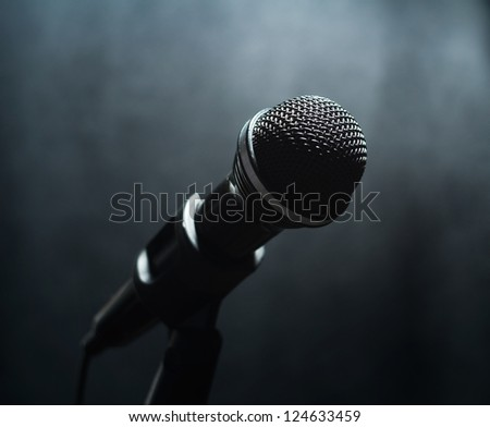Microphone in a smoke on a dark background - stock photo