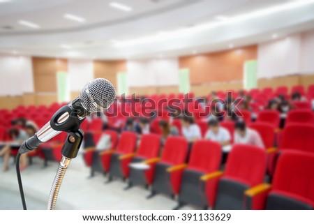 Microphone in auditorium background - stock photo