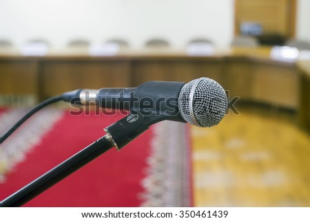 Microphone in  empty auditorium on background a red carpet. - stock photo