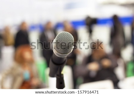 Microphone in focus against blurred audience - stock photo